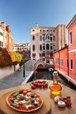 Italian pizza in Venice against canal, Italy Stock Photo
