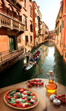 Italian pizza in Venice against canal, Italy stock photography