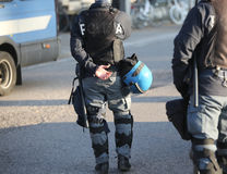 Italian police in riot gear with flak jackets and blue helmets a. Italian police in riot gear with flak jackets and protective helmets and batons Stock Photo