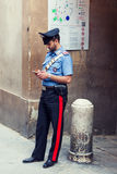 Italian policeman standing on the street. Siena, Italy - June29, 2016: Italian policeman standing on the street and checking his smartphone in Siena, Italy Stock Photos