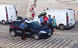 Italian policemen check documents of men Stock Images
