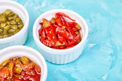 Italian preserved set - marinated capers and pepper, Sundried tomatoes. In white bowls. Mediterranean. Copy space stock images