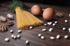 The Italian products on the tabel. 2. The Italian products  on the tabel - spaghetti, eggs, walnut, peanut, fennel, cilantro, haricot Royalty Free Stock Images