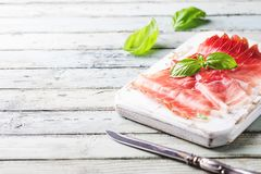 Italian prosciutto crudo. Or jamon with basil on cutting board over wooden background stock image