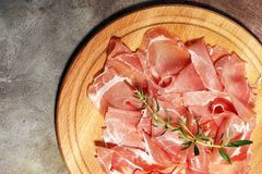 Italian prosciutto crudo or jamon with parsley. Raw ham.  stock photos