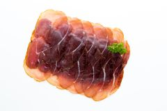Italian prosciutto crudo or jamon. Raw ham. Isolated on white ba. Ckground Royalty Free Stock Image