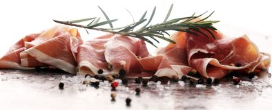 Italian prosciutto crudo or jamon with rosemary. Raw ham with spices. Italian prosciutto crudo or jamon with rosemary. Raw ham appetizer royalty free stock photography