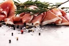 Italian prosciutto crudo or jamon with rosemary. Raw ham with spices. Italian prosciutto crudo or jamon with rosemary. Raw ham appetizer royalty free stock photo