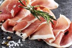 Italian prosciutto crudo or jamon with rosemary. Raw ham with spices. Italian prosciutto crudo or jamon with rosemary. Raw ham appetizer royalty free stock images