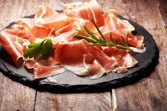 Italian prosciutto crudo or jamon with rosemary. Raw ham on wooden board. Italian prosciutto crudo or jamon with rosemary. Raw ham on wood royalty free stock photo