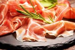 Italian prosciutto crudo or jamon with rosemary. Raw ham on wooden board. Italian prosciutto crudo or jamon with rosemary. Raw ham on wood royalty free stock images