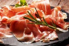 Italian prosciutto crudo or jamon with rosemary. Raw ham on wooden board. Italian prosciutto crudo or jamon with rosemary. Raw ham on wood stock photos