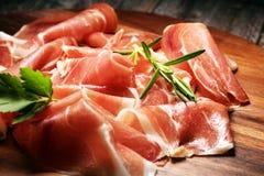 Italian prosciutto crudo or jamon with rosemary. Raw ham on wooden board. Italian prosciutto crudo or jamon with rosemary. Raw ham on wood stock images