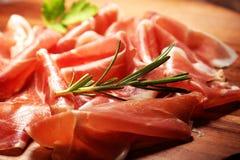 Italian prosciutto crudo or jamon with rosemary. Raw ham on wooden board. Italian prosciutto crudo or jamon with rosemary. Raw ham on wood royalty free stock photography
