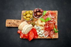 Italian prosciutto crudo or spanish jamon, cheese, olives and bread. Raw ham on cork cutting board. concrete background stock photo