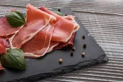 Italian prosciutto crudo or spanish jamon on a stone plate wooden background. Italian prosciutto crudo or spanish jamon royalty free stock photography