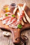 Italian prosciutto ham grissini bread sticks olive oil Royalty Free Stock Photo