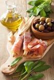 Italian prosciutto ham grissini bread sticks olive oil Royalty Free Stock Images