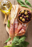 Italian prosciutto ham grissini bread sticks olive oil Stock Photography