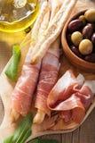 Italian prosciutto ham grissini bread sticks olive oil Royalty Free Stock Image