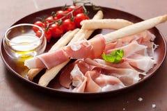 Italian prosciutto ham grissini bread sticks tomato olive oil Royalty Free Stock Photos