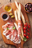 Italian prosciutto ham grissini bread sticks tomato olive oil Stock Photo