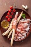Italian prosciutto ham grissini bread sticks tomato olive oil. Italian prosciutto ham grissini bread stick tomato olive oil royalty free stock image