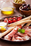 Italian prosciutto ham grissini bread sticks tomato olive oil Royalty Free Stock Photos