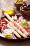 Italian prosciutto ham grissini bread sticks tomato olive oil Royalty Free Stock Photo
