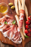 Italian prosciutto ham grissini bread sticks tomato olive oil Stock Photography