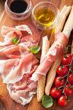 Italian prosciutto ham grissini bread sticks tomato olive oil Royalty Free Stock Photography