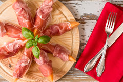 Italian prosciutto and melon with basil Stock Photos