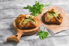 Italian puff pastry patties fagottini. Stuffed with cheese and spinach, parsley on a light background white wooden Stock Photos