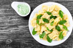 Italian ravioli with creamy spinach sauce, top view Stock Photos