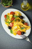 Italian ravioli with olives, tomato and rocket Stock Photos