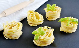 Italian raw homemade pasta tagliatelle. Black background Royalty Free Stock Photography