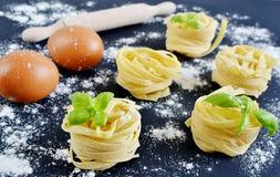 Italian raw homemade pasta tagliatelle. Black background Stock Photos