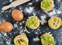 Italian raw homemade pasta tagliatelle. Black background Stock Images