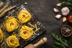 Italian raw homemade pasta tagliatelle. Fresh italian pasta tagliatelle at wooden table and ingredients for cooking. Italian food background Royalty Free Stock Photography