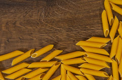 Italian raw rigatoni pasta on wooden table with copy space. top view Stock Image