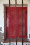 Italian Red Shutters on Stucco with Metal Bars Stock Photography