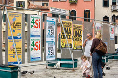 Italian referendum posters. A family reads political posters on display in Venice ahead of the Italian Referendum in June 2011 Royalty Free Stock Images
