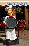 Italian restaurant. Detail of chef holding menu in front of Italian restaurant Royalty Free Stock Images