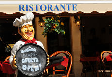 Italian restaurant. Detail of chef holding menu in front of Italian restaurant Royalty Free Stock Photos