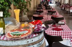 Italian restaurant. Outdoor view of traditional italian restaurant - pizza, wine and vegetables served on a wooden barrel at display Royalty Free Stock Photos