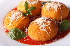 Italian rice balls in tomato sauce on a plate close-up. horizont. Italian arancini rice balls in tomato sauce on a plate close-up. horizontal Royalty Free Stock Photo