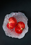 Italian ripe tomato with aluminium wrap on dark background Royalty Free Stock Image