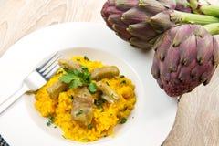 Italian risotto with artichoke. Italian risotto with saffron and artichokes Royalty Free Stock Photos