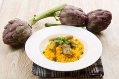 Italian risotto with artichokes. Italian risotto with saffron and artichokes Royalty Free Stock Images