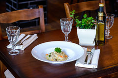 Italian risotto. In white plate on wooden table in a restaurant royalty free stock photo
